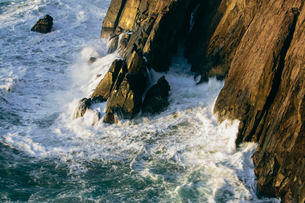 Crashing waves and surf at the base of sheer cliffs on the ocean coastline.の写真素材 [FYI02264196]