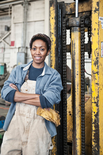 Black woman factory worker and a fork lift in a sheet metal factory.の写真素材 [FYI02264200]
