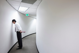 An Asian businessman frustrated and standing with his head against a wall in a hallway.の写真素材 [FYI02264218]