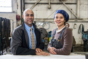 Black man owner of a sheet metal factory and a black woman factory worker going over plans at a workの写真素材 [FYI02264219]