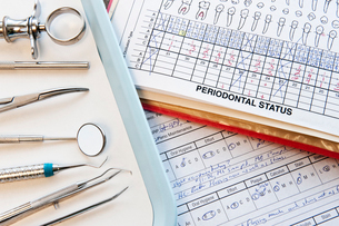 Closeup of dental tools and dental records in a dental office.の写真素材 [FYI02264221]