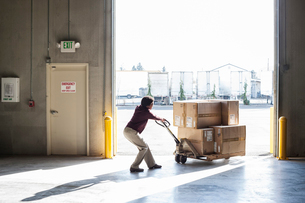 A female warehouse worker moving products in cardboard boxes by using a manual pallet jack in a distの写真素材 [FYI02264223]