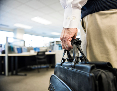 Closeup of a hand carrying a brief case in an office environment.の写真素材 [FYI02264231]