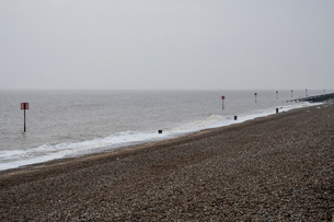 View along shingle beach with a row of partially submerged metal marker poles in the ocean.の写真素材 [FYI02264232]