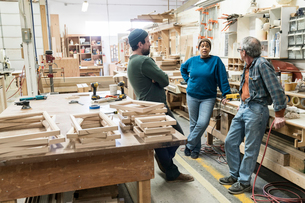 A group of mixed race carpenters discussing a project at a work station in a large woodworking shop.の写真素材 [FYI02264235]