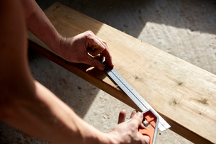 Man measuring a plank of wood using a metal ruler.の写真素材 [FYI02264238]