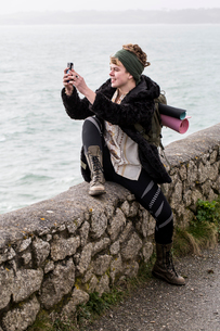Young woman with brown hair and dreadlocks wearing headscarf sitting on dry-stone wall near ocean, tの写真素材 [FYI02264244]