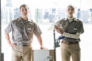 A team portrait of two Caucasian female and Hispanic male uniformed warehouse workers .の写真素材 [FYI02264245]