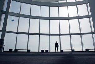 Rear view of person standing in front of tall glass wall.の写真素材 [FYI02264251]