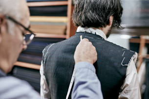 Tailor using measuring tape on a suit jacket, fitting the garment on a customerの写真素材 [FYI02264252]