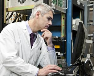 A male Caucasian technician working over a problem in a technical research and development site.の写真素材 [FYI02264259]