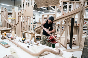 Caucasian carpenter working on a spiral staircase railing in a large woodworking shop.の写真素材 [FYI02264262]