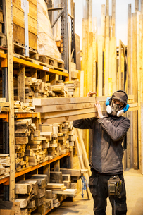 Man wearing ear protectors and dust mask standing in a warehouse, carrying long planks of wood on hiの写真素材 [FYI02264274]