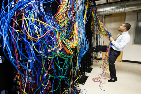 A black male technician pulling on a tangled mess of CAT 5 cables in a computer server room.の写真素材 [FYI02264275]