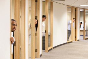 Individual business people looking out the doorway of their offices.の写真素材 [FYI02264278]