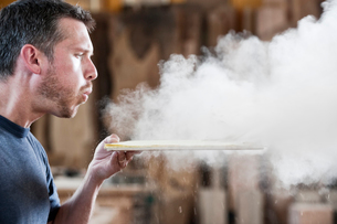 Caucasian man factory worker blowing sanding dust off a wooden piece in a woodworking factory.の写真素材 [FYI02264283]