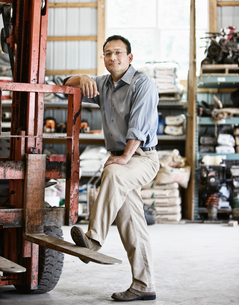 Hispanic man owner of a landscape company standing in the equipment roomの写真素材 [FYI02264284]