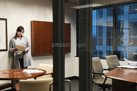 A Mixed Race woman working in an office, viewed through a glass doorway.の写真素材 [FYI02264310]