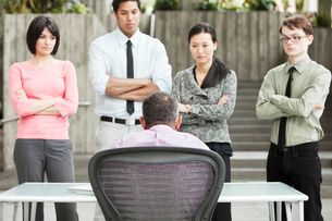 A mixed race group of business people standing in front of a person at a desk.の写真素材 [FYI02264314]