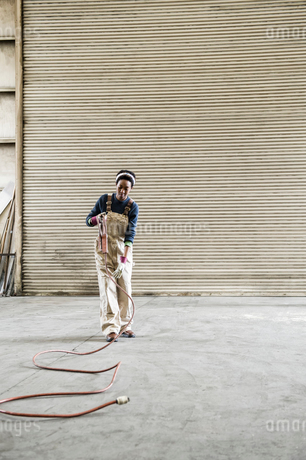 Black woman factory worker gathering tools together on the floor of a sheet metal factory.の写真素材 [FYI02264315]