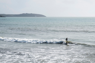 Surfer wearing wet suit riding ocean wave close to shore.の写真素材 [FYI02264323]