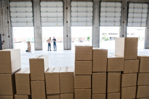 Team of workers check out inventory in front of loading dock doors in a new warehouse.の写真素材 [FYI02264328]