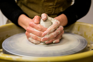 Close up of potter wearing apron working on pottery wheel, shaping clay.の写真素材 [FYI02264329]