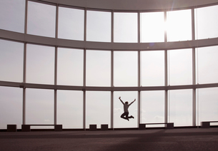 Rear view of person jumping in the air in front of tall glass wall.の写真素材 [FYI02264330]