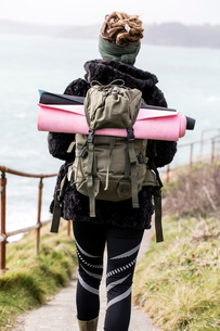Rear view of young woman with brown hair and dreadlocks carrying backpack, walking along coastal hikの写真素材 [FYI02264335]