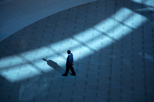 High angle view of man standing in foyer of building, casting shadow.の写真素材 [FYI02264337]
