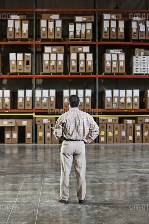 A storeroom manager looking at stock stacked high on shelves with his hand on his hip.の写真素材 [FYI02264341]