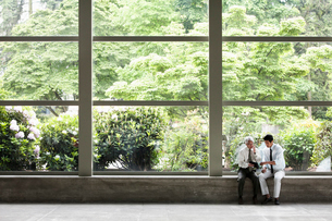 Two businessmen working on a notebook computer and sitting in front of a large window in the lobby oの写真素材 [FYI02264350]