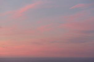 View over the ocean and the sunset sky with pink cloud at dusk.の写真素材 [FYI02264368]