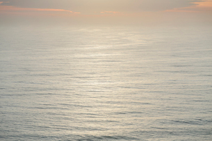 The open ocean, water surface calm and grey and the glow of the sun at dawn on the horizon.の写真素材 [FYI02264371]