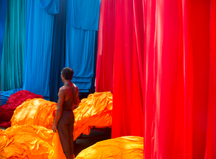 High angle view of person standing in between bright and vibrant heaps of blue, red and orange fabriの写真素材 [FYI02264380]