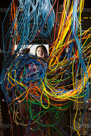 Asian female technician working on a tangled mess of CAT 5 cables in a server room.の写真素材 [FYI02264397]