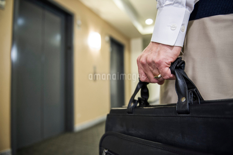 Closeup of a hand carrying a brief case in an office environment.の写真素材 [FYI02264398]