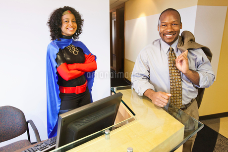 A black businesswoman office super hero and her black businessman partner in their office.の写真素材 [FYI02264405]