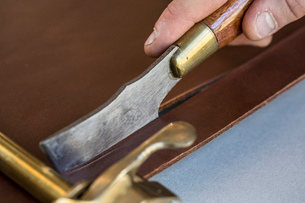 High angle close up of craftsman making brown leather camera strap using a hand tool on the leatherの写真素材 [FYI02264416]