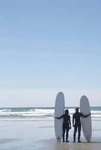 Rear view of man and woman wearing wet suits standing side by side on sandy beach by the ocean, holdの写真素材 [FYI02264418]