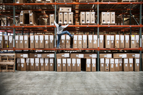 A warehouse worker trying to climb a rack of products in a distribution warehouse.の写真素材 [FYI02264422]