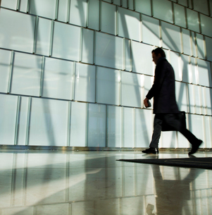 Silhouette of man carrying briefcase walking past glass wall.の写真素材 [FYI02264430]