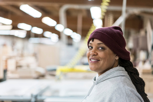 Portrait of a Black woman carpenter in a large woodworking shop.の写真素材 [FYI02264439]