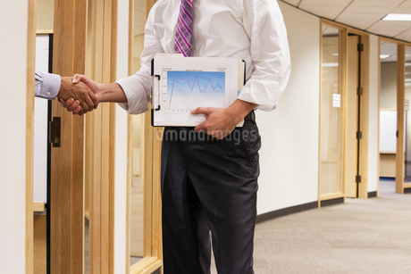A closeup view of two business people shaking hands in an office space.の写真素材 [FYI02264440]