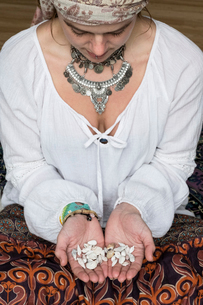High angle view of woman wearing white blouse headscarf sitting on floor, holding seashells.の写真素材 [FYI02264443]