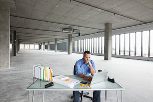A Caucasian male business owner at his temporary desk in a new raw business space.の写真素材 [FYI02264445]