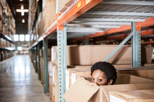 A black female worker hiding inside a cardboard box in a distribution warehouse.の写真素材 [FYI02264448]