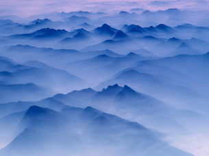 Aerial view of mountain range covered in mist at twilight.の写真素材 [FYI02264449]