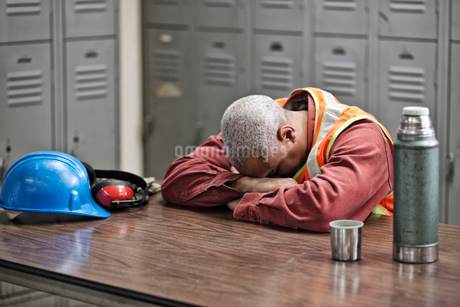 Black man factory worker taking a break from work in a factory locker room.の写真素材 [FYI02264452]