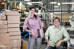 A portrait of a team of two Caucasian male and female workers in a parts department work siteの写真素材 [FYI02264464]